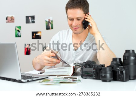 Photographer discussing photos with client by mobile phone.