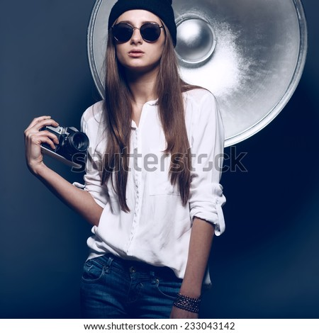 Photographer girl with glasses and a hat with a camera in the studio