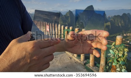 photographer holding a nd graduated filter and graduated filter - stock photo