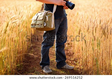 Photographer holding camera on wheat fields in warm sunset - stock photo