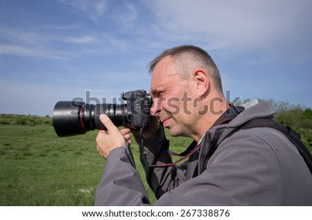 Photographer in action with backpack in nature - stock photo