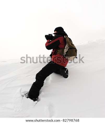 Photographer in extreme conditions getting picture of mountain view - stock photo