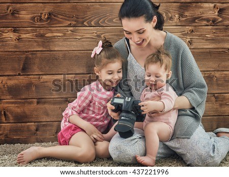 Photographer in motion. Young woman photographer and children girls having fun at the photo session. - stock photo