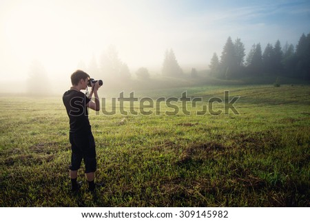 photographer in the fog taking a picture of the landscape - stock photo