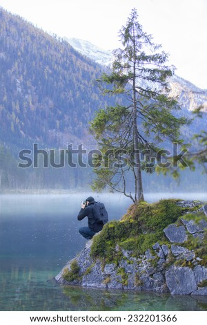 photographer is standing on a little island with a fir tree. He is taking a picture of the foggy sea with his cristal clear water. - stock photo