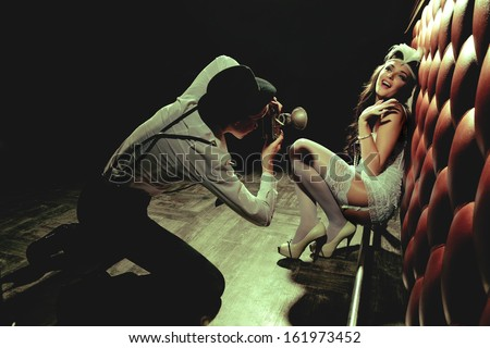 Photographer is taking a picture of a beautiful cabaret girls - stock photo