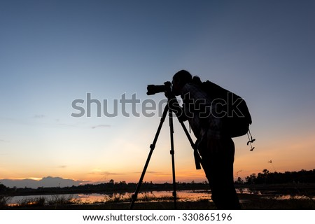 photographer is taking a picture of landscape sunset - stock photo