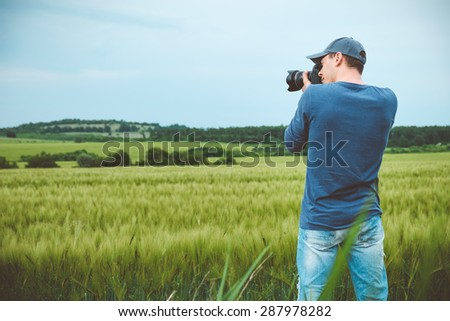 Photographer is taking a picture of scenic landscape. - stock photo