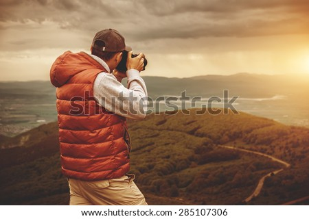 Photographer is taking a picture of  sunset in mountains - stock photo