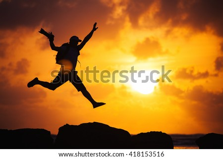 Photographer jumping on the cliff at sunset time