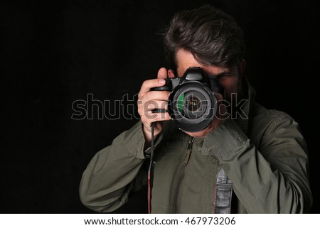 Photographer looking into the camera takes picture. Close up. Black background