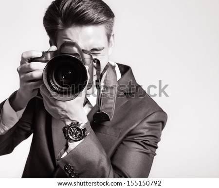 Photographer man is using professional camera - stock photo