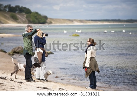 Photographer, model and director at a shoot on the beach - stock photo