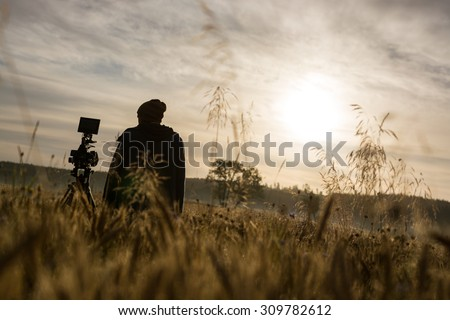 Photographer or filmmaker early in the morning honing his craft. Going that extra mile for a good shot.  - stock photo