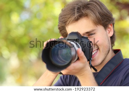 Photographer photographing and learning with a dslr digital camera with a green background                 - stock photo