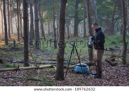 Photographer preparing to take some photos in a forest - stock photo
