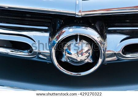 Photographer reflected in an old chrome car bumper - stock photo