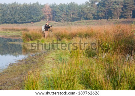 Photographer setting up the shot in a bog - stock photo