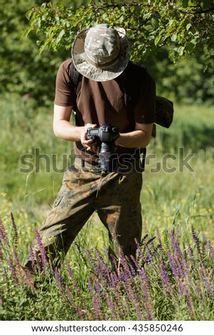 Photographer shooting flowers with DSLR camera in forest - stock photo
