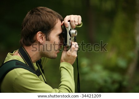 Photographer shooting with compact camera in forest. Shallow DOF. - stock photo