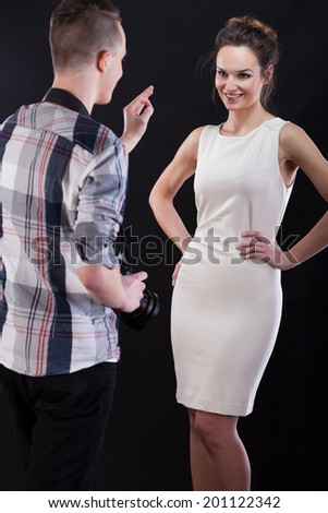 Photographer showing ok gesture to his female model during work - stock photo