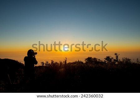Photographer silhouette against sunrise in mountain - stock photo
