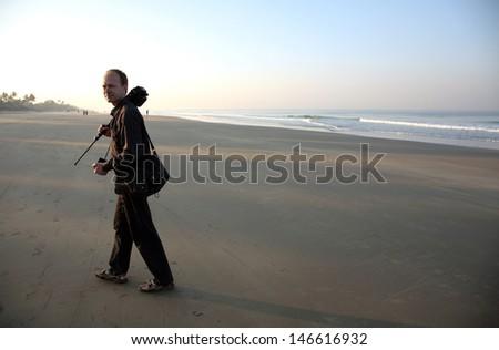 Photographer silhouette, exotic beach, India - stock photo
