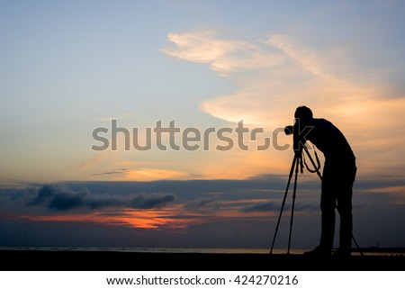 Photographer silhouette in outdoor with dramatic sunset. - stock photo