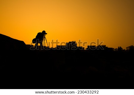 Photographer silhouette shooting outdoors at sunset background - stock photo