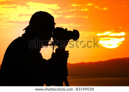 Photographer silhouette shooting sea outdoors at sunset background - stock photo