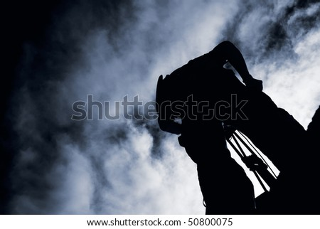 Photographer silhouette stand with dramatic clouds and working. - stock photo
