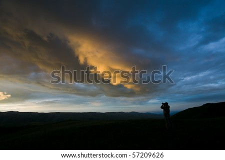 Photographer (Silhouette) takes a snapshot of clouds at sunset