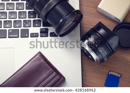 Photographer studio, camera lens, sd cards, portable power bank, laptop on table.  - stock photo