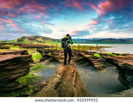 Photographer take a picture of sunset on the volcanic origin peninsula - Dyrholaey , south coast of Iceland, near Vik village, Europe. Artistic style post processed photo.