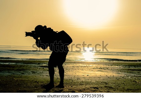 Photographer takes a picture during sunrise at the beach - lifestyle concept - stock photo