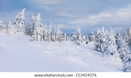 Photographer takes a picture in winter mountains - stock photo