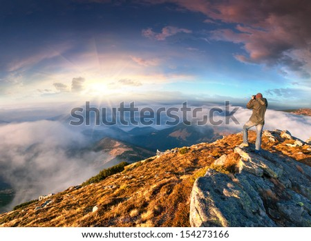 Photographer takes a sunset in the mountains - stock photo