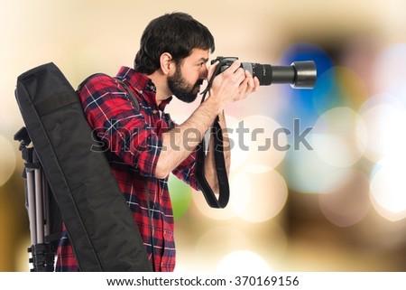 Photographer taking a photo on unfocused background - stock photo