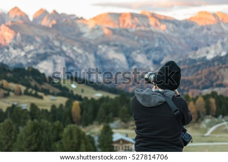 Photographer taking a picture over the Dolomites Alps-Italy. (Passo sella)