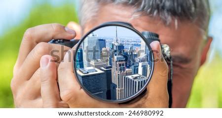 Photographer taking photo with DSLR camera at Manhattan skyline. Shallow DOF - stock photo