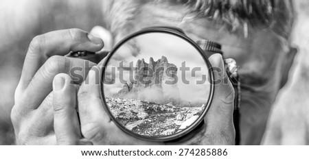 Photographer taking photo with DSLR camera at Mountain peak. Shallow DOF - stock photo