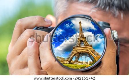 Photographer taking photo with DSLR camera at Tour Eiffel. Shallow DOF - stock photo