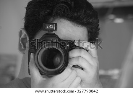 Photographer taking photo with his camera in black and white monochrome