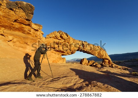 Photographer taking picture of Sunset Arch, Grand Staircase-Escalante National Monument, UT - stock photo