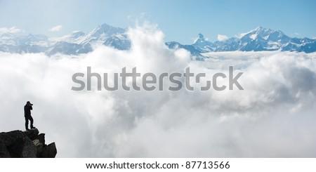 photographer taking picture of Swiss Alps, peak of Matterhorn on the horizon, Switzerland - stock photo