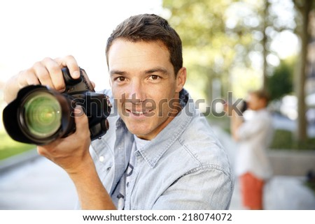 Photographer taking pictures in the street - stock photo