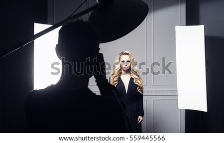 Photographer taking pictures of a beautiful model in studio. Fashion, beauty, glamour concept.