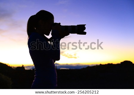 Photographer taking pictures with SLR camera at night. Nature landscape photographer with telephoto lens. Silhouette of woman taking photo after sunset. - stock photo