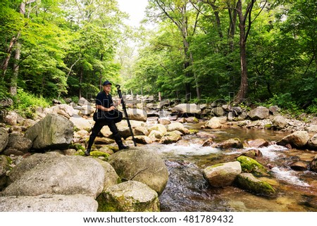 Photographer traveler on a mountain river in the wild