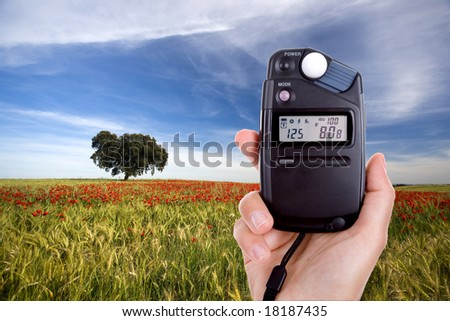 photographer using lightmeter to measure correct light setup in landscape photo
